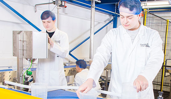 Photo of two students working on a simulated production line at Carlisle College Advanced Manufacturing Centre