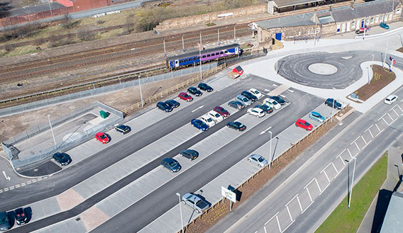 Aerial photograph of train station and adjacent car park