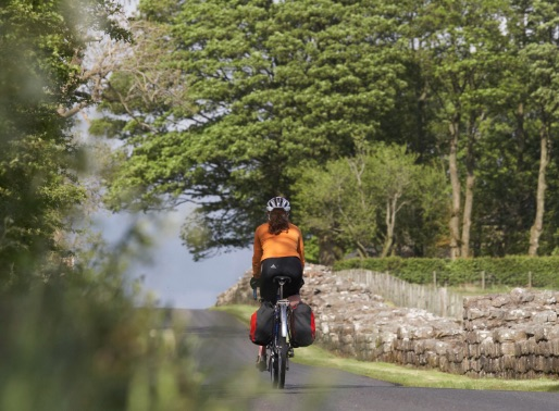 Photo of a woman cycling along a picturesque path