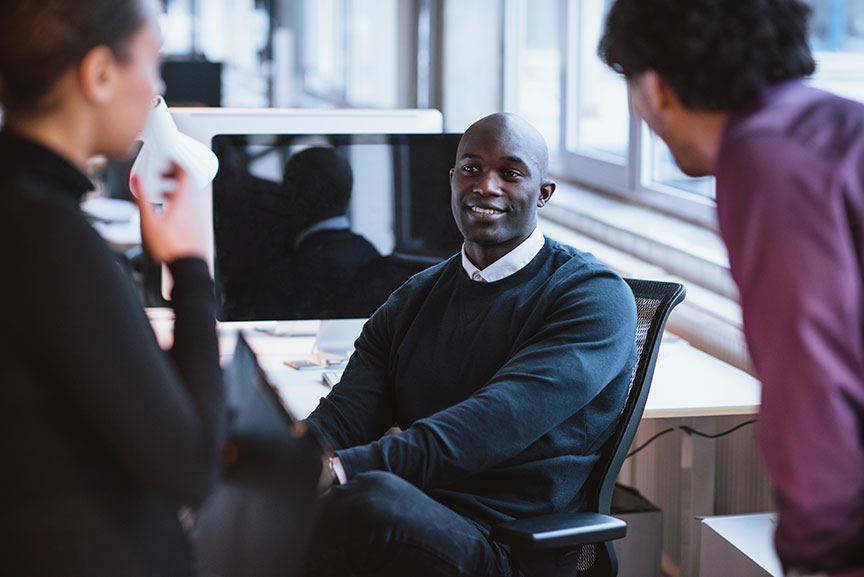 Photo of man sitting in a desk chair talking to collegues