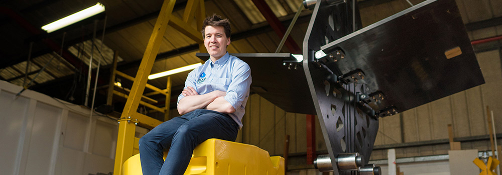 Photo of sitting, smiling man in warehouse with equipment behind him