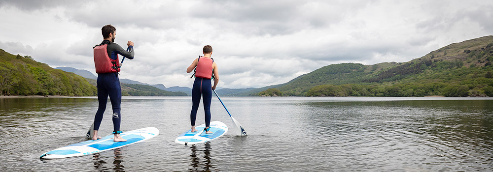 Panoramic photo of man and woman on wakeboards paddling out onto lake
