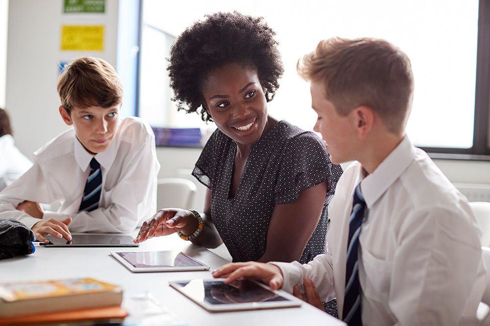 Photo of teacher and two pupils at a school desk